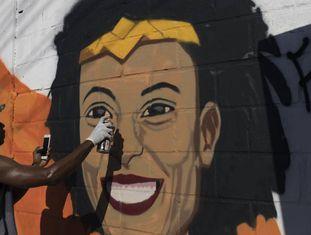 O grafiteiro Aria Crespo pinta um mural com a imagem da vereadora do PSOL Marielle Franco