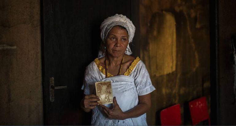 Mãe Merinha segura uma das fotos que sobrou do incêndio