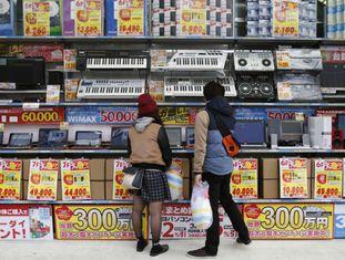 Jovens observam vitrine de uma loja em Tóquio.