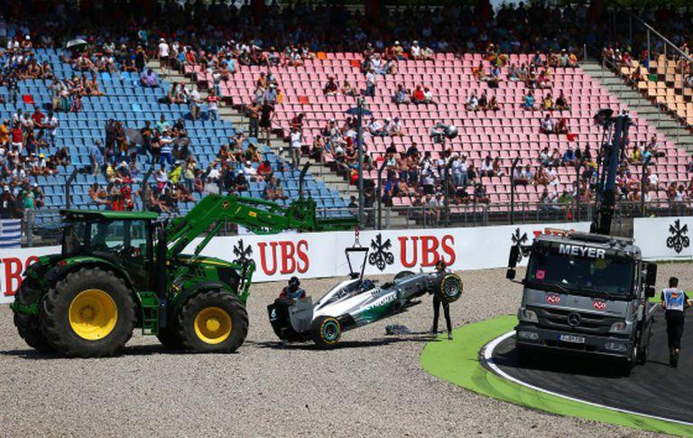 O carro de Hamilton é retirado depois do acidente.