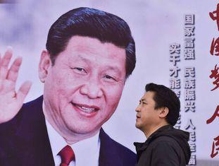 Homem passa por um cartaz do presidente chinês Xi Jinping em Pequim