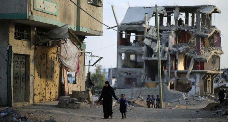 Uma mãe e seu filho, nas ruínas de Gaza.
