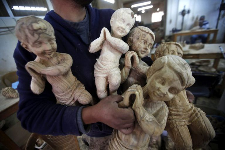 Carpinteiro mostra figuras cristãs em uma oficina em Belém, Palestina.