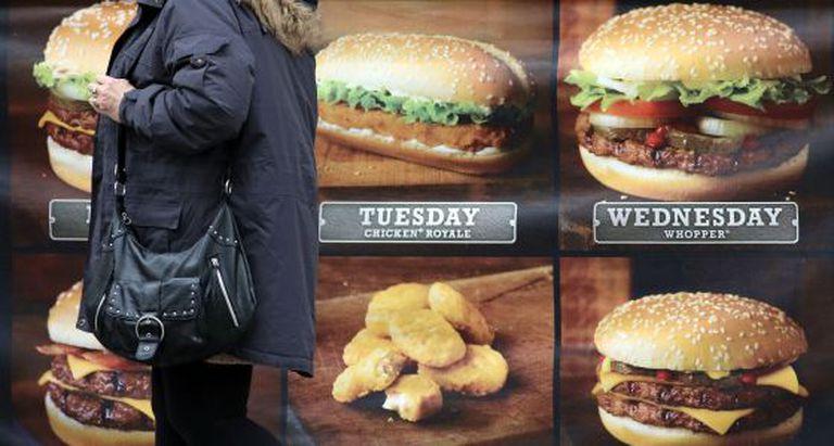 Uma mulher diante de um anúncio de fast food.