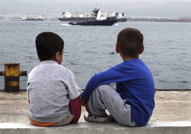 Dois meninos refugiados observam o mar, na Grécia.