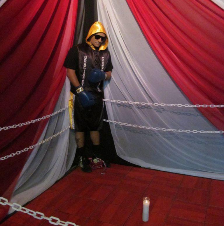 Christopher Rivera com seu traje e luvas de boxeador sobre o ringue.