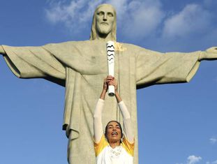 A campeã olímpica Isabel, do vôlei de praia, leva a tocha ao Cristo Redentor, nesta sexta-feira, no Rio.