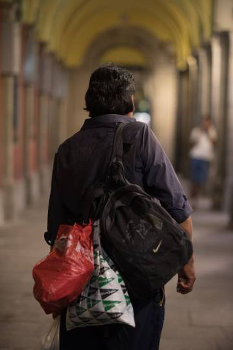 Raúl posa com seus pertences nos pórticos da Plaza Mayor.