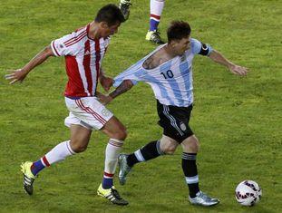 O meia paraguaio Victor Cáceres tentar frear Messi puxando sua camiseta durante o jogo de sábado.