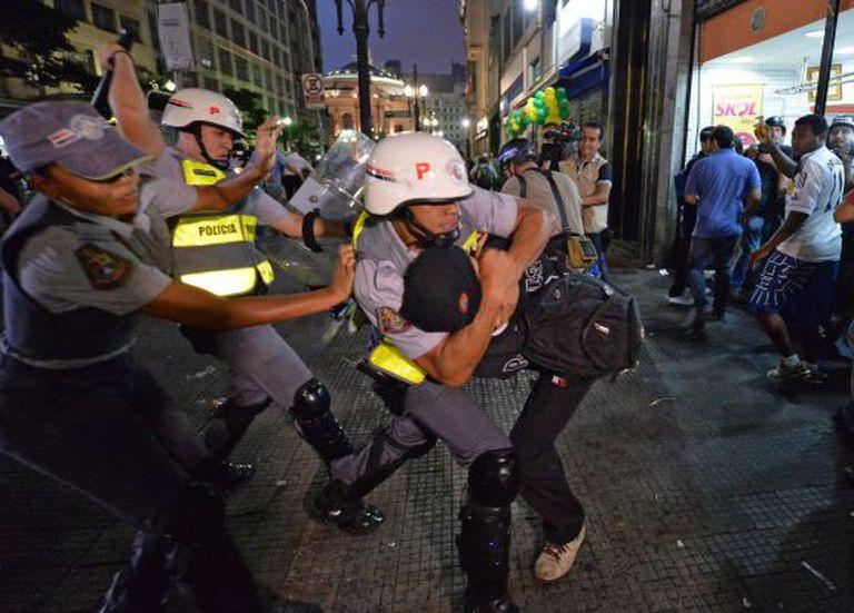 Policial militar agride manifestante durante protesto contra a Copa do Mundo em 22 de fevereiro deste ano, em São Paulo.