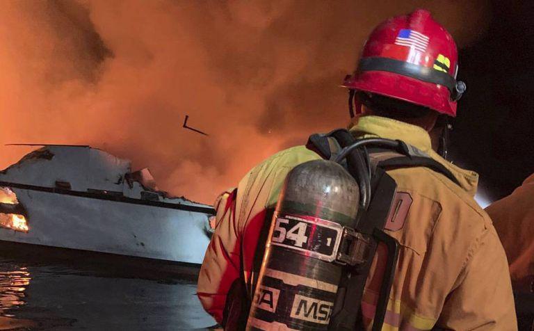 Um bombeiro trata de extinguir o incêndio declarado nesta segunda-feira em um barco em Califórnia.