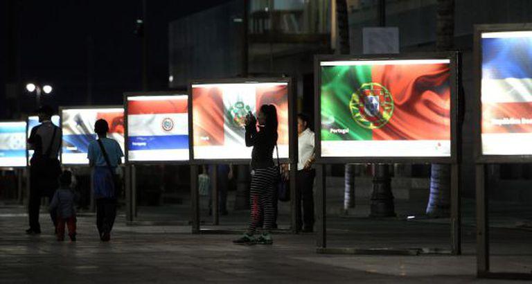 Visitantes junto às bandeiras dos países participantes da cúpula.