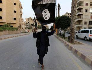 Em junho de 2014, um membro armado do Estado Islâmico acenando uma bandeira na cidade síria de Raqqa, reduto da organização jihadista.
