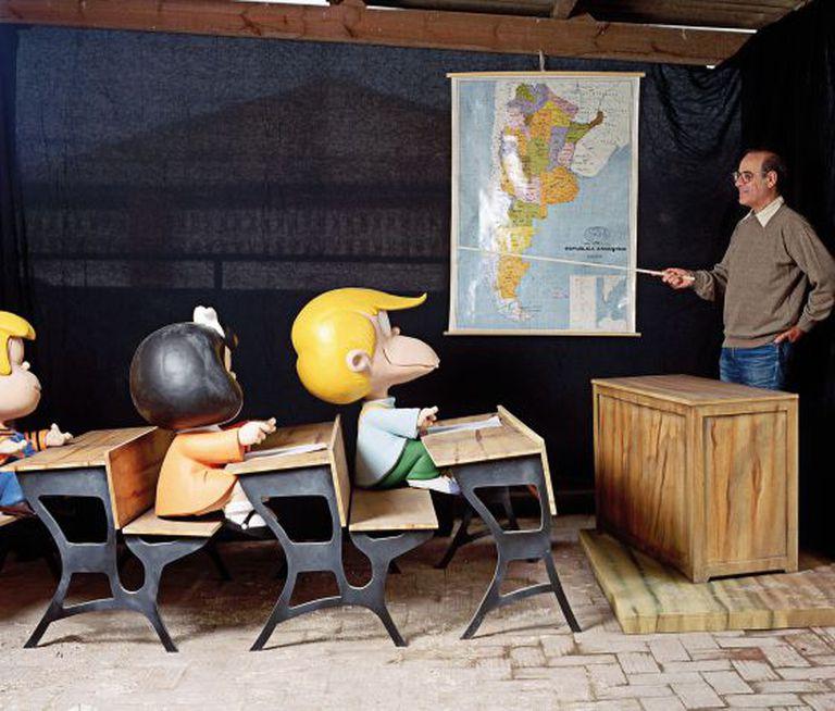 O desenhista em uma foto antiga, na qual simula dar aula a alguns dos personagens da sua mais famosa tira humorística.