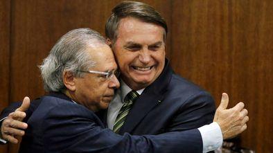 Paulo Guedes abraça Bolsonaro.