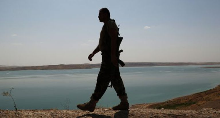 Um soldado curdo patrulha a represa de Mossul.