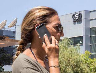 Uma mulher fala pelo celular diante do edifício do NSO Group, perto de Tel Aviv (Israel).