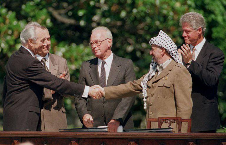 O então chanceler Shimon Peres (esq.) cumprimenta o presidente da Organização para a Libertação da Palestina, Yasser Arafat (dir.), durante a assinatura do acordo de paz do Oriente Médio de Washington, em 1993.