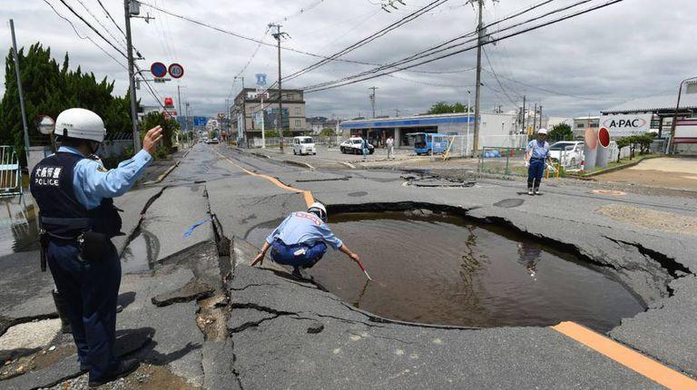 Policial examina cratera aberta pelo terremoto em uma rua de Takatsuki, ao norte de Osaka, na manhã desta segunda-feira