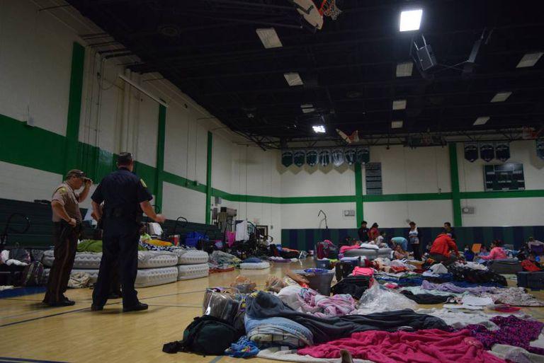 Membros da Policial observam a pessoas em um dos refúgios anti furacão de Miami.