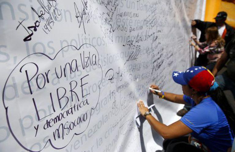 Vários oposicionistas escrevem em um mural, em um protesto em 28 de fevereiro em Caracas.