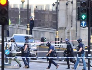 Agentes da policial antiterrorismo atravessam a zona isolada nesta quarta-feira na Ponte de Westminster, em Londres, em proximidade da sede do Parlamento britânico.