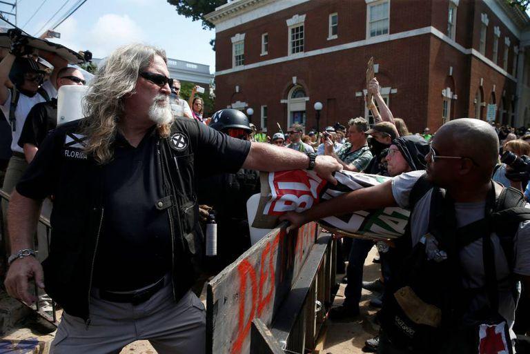 Supremacista branco agarra a faixa de um protestante que luta contra o racismo na Virgína (EUA)