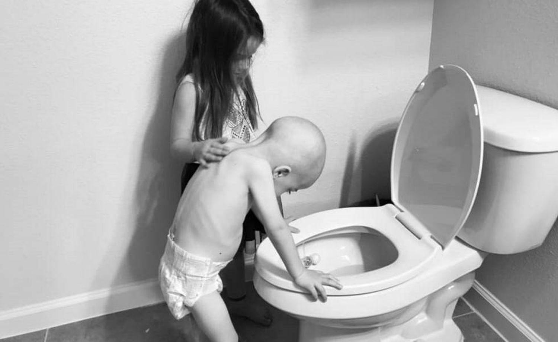 Foto em que se vê como Audrey (5 anos) consola o irmão de quatro.
