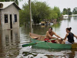 Um casal uruguaio rema um bote nas ruas inundadas de Durazno em 2010.