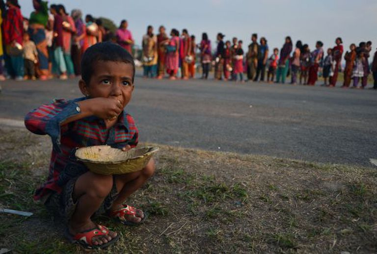 Uma criança come arroz em um campo de refugiados nepalíes.