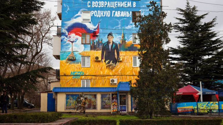 """Um mural sobre Putin em Sebastopol: """"Bem-vindo de volta ao porto da pátria""""."""