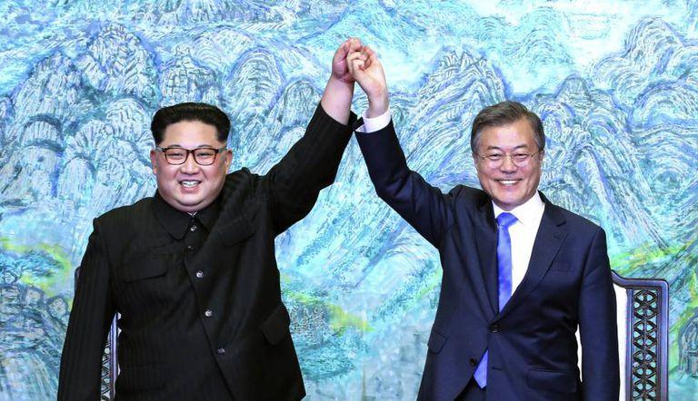 O presidente da Coreia do Norte, Kim Jong-un, e o da Coreia do Sul, Moon Jae-in, levantam os braços durante o encontro de sexta-feira