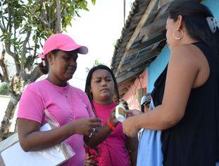 Funcionária distribui repelentes e preservativos a várias mulheres em Barranquilla, na Colômbia, na campanha contra o zika.