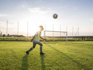 Uma criança joga com sua bola.