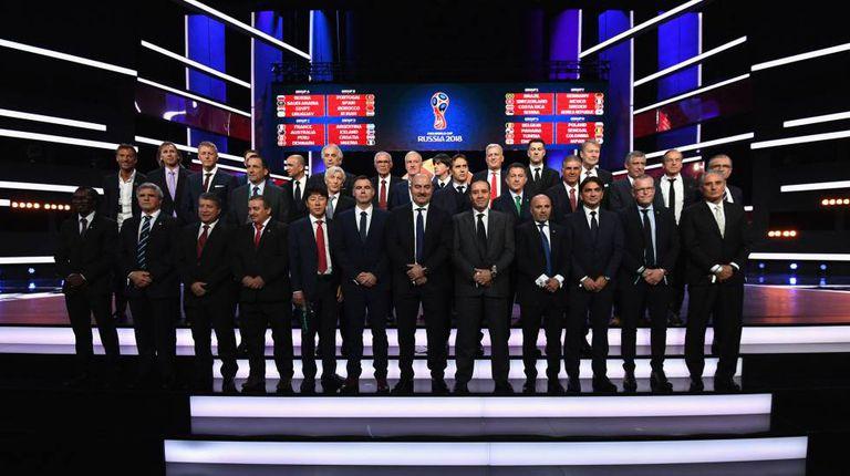 Os treinadores das seleções classificadas posam para foto no palco onde foi realizado o sorteio.