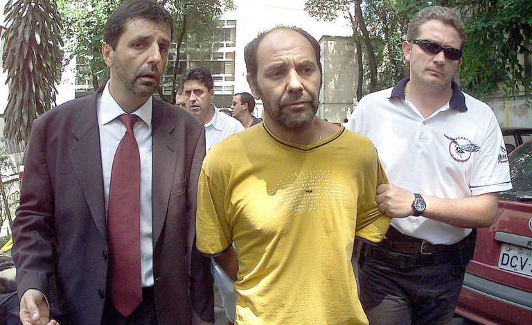 O líder dos sequestradores do publicitário Washington Olivetto, o chileno Maurício Hernandez Norambuena (c), é levado preso por policiais para ser apresentado na Delegacia Antissequestro (DEAS), em São Paulo, no dia 4 de fevereiro de 2002.