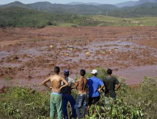 Moradores observam ruas tomadas por lama.