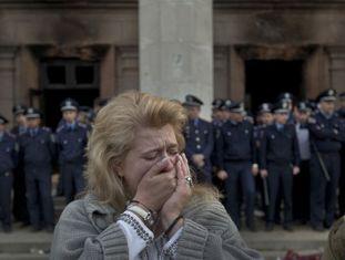 Uma mulher chora em frente ao edifício em Odessa onde morreram os ativistas.