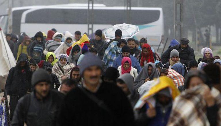 Imigrantes e refugiados cruzam fronteira sob chuva.