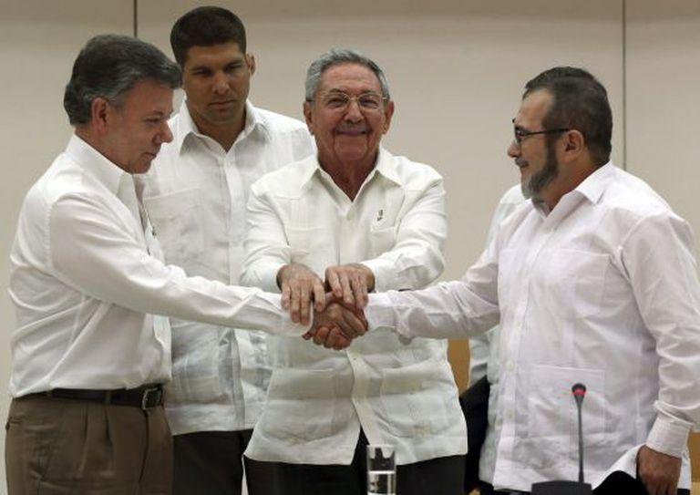 O presidente de Cuba, Raúl Castro (no centro), aperta as mãos do presidente da Colômbia, Juan Manuel Santos (à esquerda), e o líder máximo das FARC, Rodrigo Londoño, 'Timochenko', em Havana na quarta-feira.