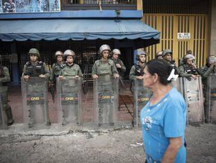 Agentes da Guarda Nacional Bolivariana protegem uma loja em Táchira.