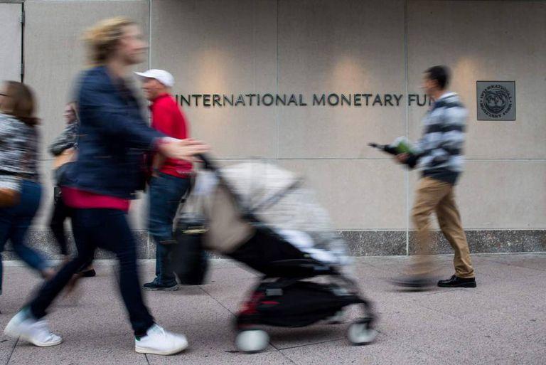 Transeúntes passam em frente à sede do FMI em Washington.