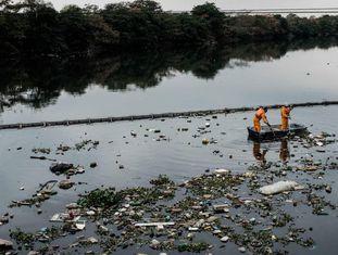 O eco-barcos recolhem os vertidos que se têm colado pela barreira na baía de Guanabara.
