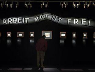 """Uma sala da exposição, com o cartaz da entrada do campo de Auschwitz, onde se lê """"O trabalho liberta""""."""