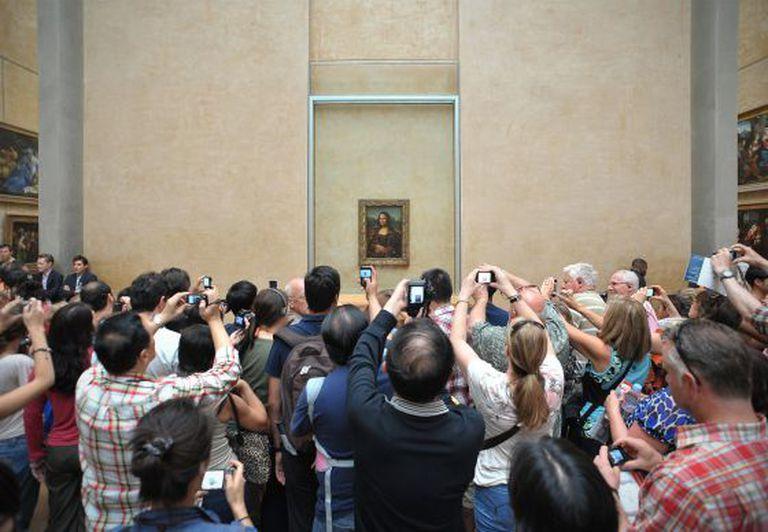 Turistas fotografam a Monalisa.