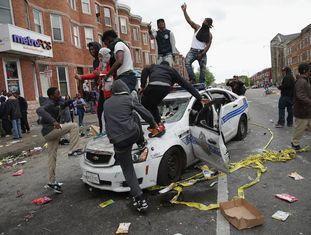 Manifestantes de Baltimore destroem um carro de polícia.