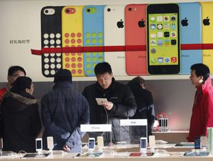 Clientes verificam dispositivos em uma loja da Apple em Pequim.