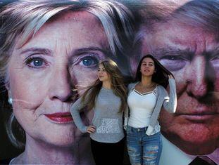 Estudantes diante de cartaz de Clinton e Trump.