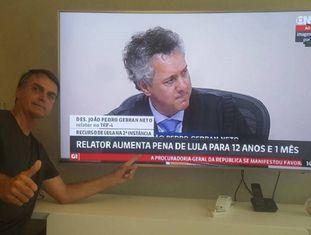 Jair Bolsonaro posa para foto diante da tela com o julgamento no TRF-4, no momento em que o relator, Gebran Neto, apresentava seu voto.