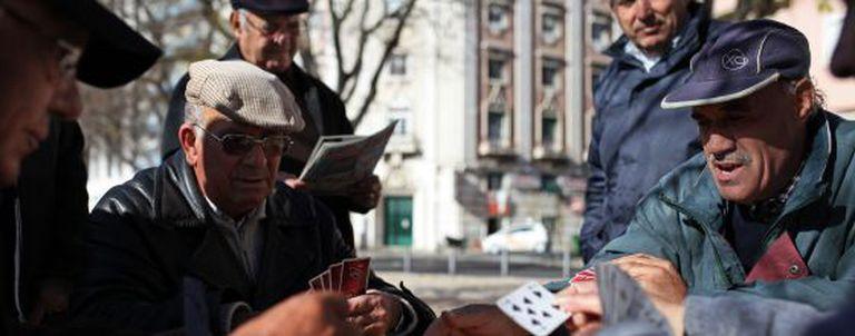 Aposentados portugueses jogam cartas em um parque de Lisboa.